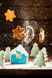 Le paysage d'hiver avec des maisons des biscuits et les arbres de Noël musardent des étoiles Photo stock