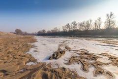 Le paysage d'hiver, avec la rivière et la glace congelées a couvert des dunes de sable, un jour ensoleillé froid photos stock