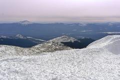 Le paysage de montagne des Monts Oural du nord avec le ciel rosâtre de coucher du soleil, les crêtes de montagne et le firn de so Images libres de droits