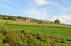 Le paysage de vallées de West Yorkshire avec des fermes sur de hautes collines avec les champs murés typiques et amarre dans la d photographie stock