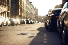 Le paysage de ville de la rue sur laquelle il y a les voitures garées images stock