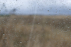 Le paysage naturel en dehors de la fenêtre avec la pluie chute sur le verre Photo libre de droits