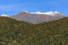 Le paysage scénique d'automne de l'arête principale de Caucase avec la crête de montagne neigeuse complète sur le fond de ciel bl photographie stock libre de droits