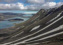 Le paysage stupéfiant du lac Langisjor, du glacier de Vatnajokull et de la neige s'est recroquevillé les pentes volcaniques noire image stock
