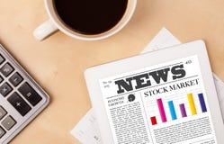 Le PC de comprimé montre des actualités sur l'écran avec une tasse de café sur un bureau Photo stock
