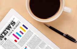 Le PC de comprimé montre des actualités sur l'écran avec une tasse de café sur un bureau Photos stock