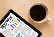 Le PC de comprimé montre des actualités sur l'écran avec une tasse de café sur un bureau Images libres de droits