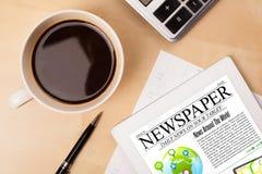 Le PC de comprimé montre des actualités sur l'écran avec une tasse de café sur un bureau Photo libre de droits