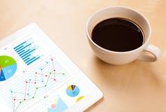 Le PC de comprimé montre des diagrammes sur l'écran avec une tasse de café sur un bureau Images stock