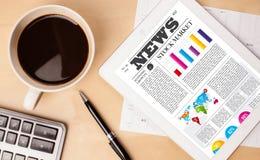 Le PC de Tablette montre des actualités sur l'écran avec une tasse de café sur un bureau Images stock