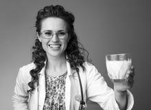 Le pediatrist de sourire soignent donner le verre de lait dessus photos libres de droits