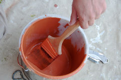 Le peintre applique la peinture orange au balai à partir du seau photographie stock