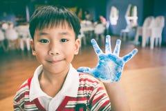 Le peintre asiatique montre ses paumes peintes sur la classe d'art Éducation Photos stock