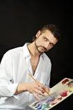 Le peintre avec la palette et les brosses regarde vers Image libre de droits