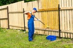 Le peintre décore la barrière en bois avec la peinture jaune Photographie stock