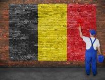 Le peintre de Chambre peint le drapeau de la Belgique sur le mur de briques Photographie stock libre de droits
