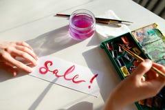 Le peintre de fille écrit avec la brosse et peint l'inscription sur la feuille, Images stock