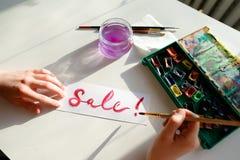Le peintre de fille écrit avec la brosse et peint l'inscription sur la feuille, Photo libre de droits