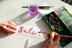 Le peintre de fille écrit avec la brosse et peint l'inscription sur la feuille, Photos libres de droits