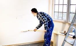 Le peintre de maison de travailleur a peint les murs dans le blanc photo stock
