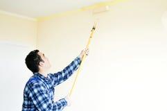 Le peintre de maison de travailleur peint un mur photographie stock