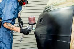 Le peintre de voiture peint l'amortisseur d'une voiture images libres de droits