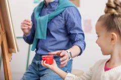 Le peintre mûr gai enseigne l'enfant à dessiner Photos libres de droits