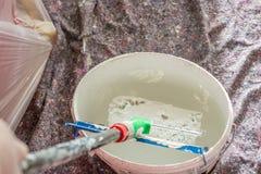 Le peintre mouille le rouleau de peinture avec la peinture blanche de mur images libres de droits