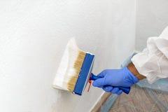 Le peintre peint le mur avec la teinte du blanc Photographie stock libre de droits