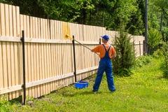 Le peintre travaille à la barrière en bois Images libres de droits