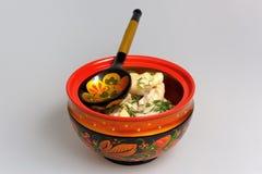 Le pelmeni bouilli dans le khokhloma a peint la cuvette en bois russe avec la cuillère images stock