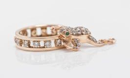 Le pendant d'or sous forme de grenouille rampe dans un anneau d'or Images stock