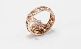 Le pendant d'or sous forme de grenouille rampe dans un anneau d'or Photo libre de droits