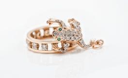Le pendant d'or sous forme de grenouille rampe dans un anneau d'or Photos libres de droits