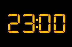 Le pendule à lecture digitale électronique avec des nombres oranges sur un fond noir montre le temps Vingt-trois heures zéro la n photos libres de droits
