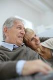 Le pensionärer som kopplar av i soffan som ser in mot framtid Arkivfoto