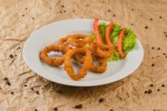 Le pepite del formaggio sul piatto sulla carta del mestiere backgroundfried gli anelli del calamaro sul piatto fotografia stock libera da diritti