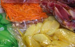 Le pere delle mele delle carote ed altri frutti sono imballati sotto vuoto in lei Fotografia Stock Libera da Diritti