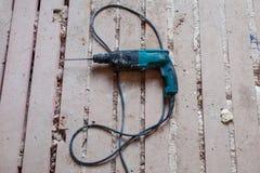 Le perforateur électrique est sur le plancher en bois sale et poussiéreux pendant la rénovation, la retouche et la construction d Photo libre de droits