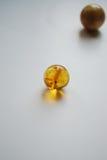 Le perle ambrate da solo si chiudono su su fondo bianco fotografia stock