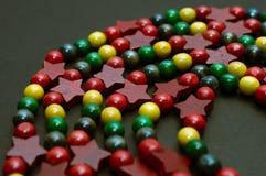 Le perle di legno Colourful di Natale hanno sistemato su una superficie neutrale Fotografia Stock Libera da Diritti