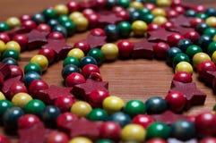Le perle di legno Colourful di Natale hanno sistemato in una spirale su una superficie di legno Fotografia Stock Libera da Diritti