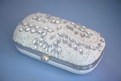 Le perle ed il cristallo di rocca isolati hanno abbellito la frizione, su un panno blu della pelle scamosciato immagini stock libere da diritti
