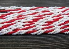 Le perle rosse e bianche del seme si chiudono su fotografia stock