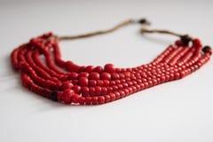 Le perle rosse stanno trovando su una tavola bianca immagini stock