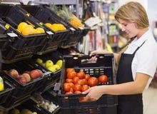 Le personalkvinnan som rymmer en ask med nya grönsaker Arkivbild