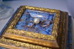 Le persone appena sposate degli anelli di oro sono accanto alle perle bianche Fotografia Stock Libera da Diritti