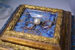Le persone appena sposate degli anelli di oro sono accanto alle perle bianche Immagine Stock