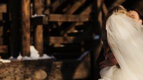 Le persone appena sposate si riscaldano nella neve in un parco dell'inverno archivi video