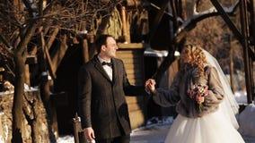 Le persone appena sposate si riscaldano nella neve in un parco dell'inverno video d archivio